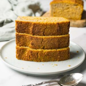 Tower of pumpkin bread slices served on a round plate, a loaf of bread on the background.