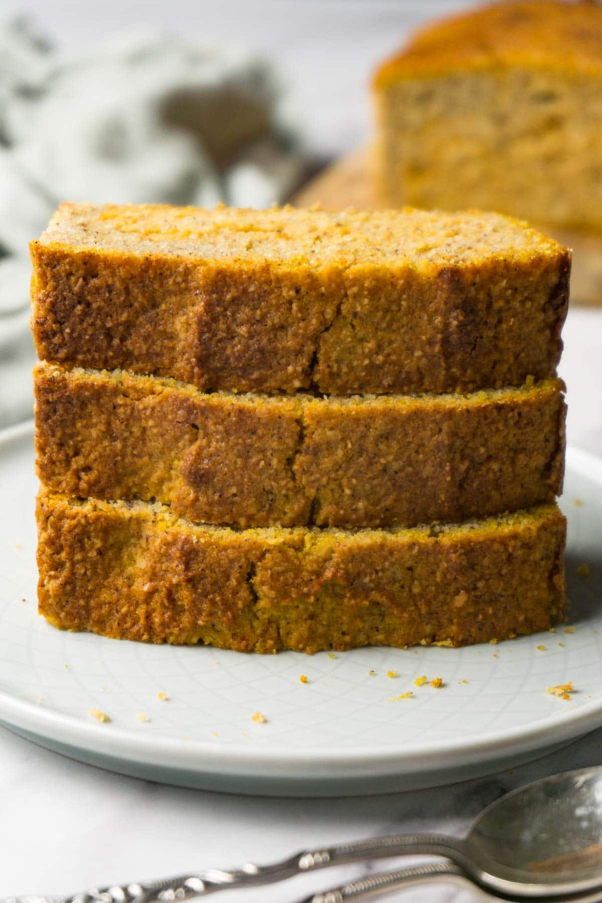 Three slices of gluten-free pumpkin bread stacked on top of each other, served on a small round plate.
