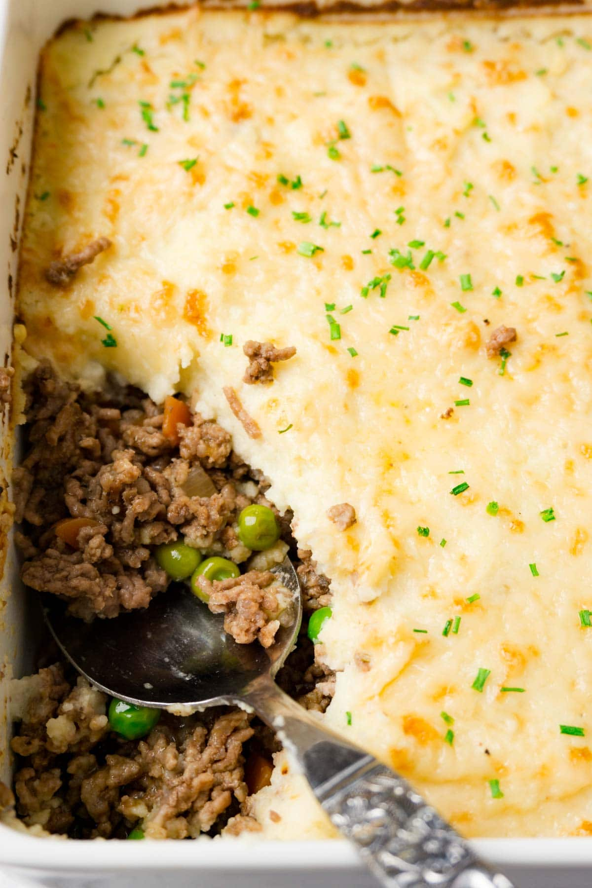 Casserole dish with freshly baked shepherd's pie garnished with chives, one piece takes with a spoon.