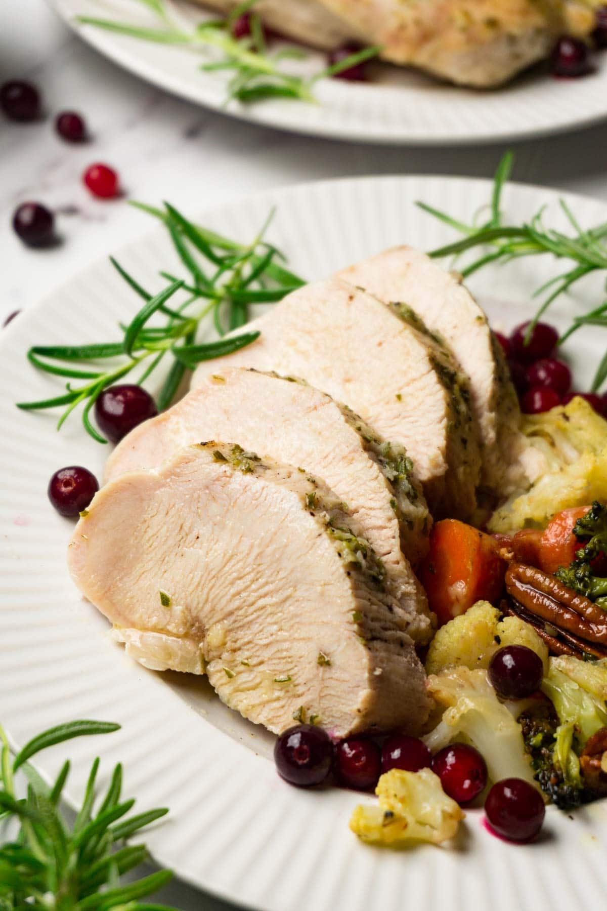 A plate with sliced brined turkey breast and stuffing on the side.