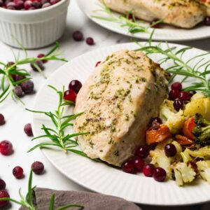 Roasted skinless turkey breast with served with fresh cranberries and cauliflower stuffing on the side.