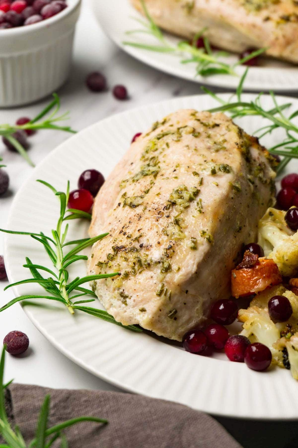 Close up shot of a roasted skinless boneless turkey breast served with stuffing and cranberries on the side.
